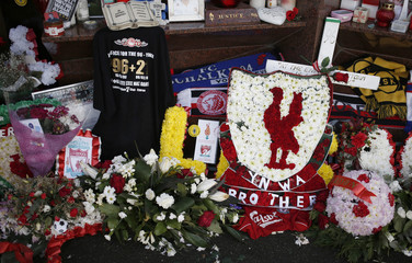 Floral tributes lie beneath the Hillsborough memorial at Anfield in Liverpool