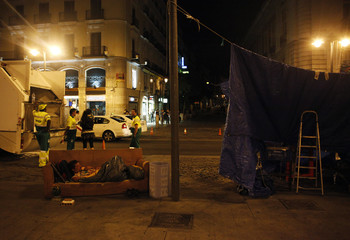 A demonstrator sleeps on a couch next to a cleaning crew at the end of his last day camping out at Puerta del Sol