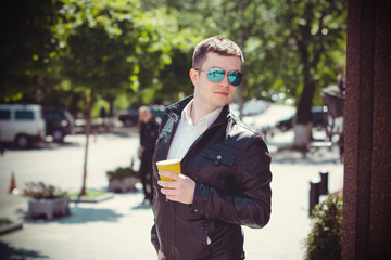 Young man townspeople in black jacket walking around the European city, drinking coffee enjoying life and views of the city