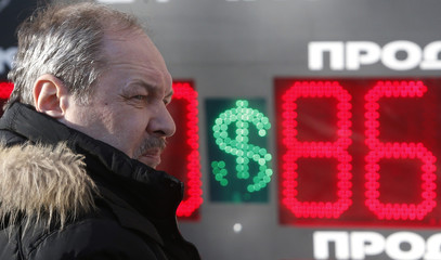 A man looks on near a board showing currency exchange rates of the U.S. dollar against the rouble in Moscow