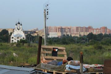 A migrant worker watches a film on his laptop on top of a shelter outside Moscow