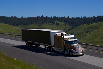 A Bronze Freightliner Semi Tractor with an extended sleeper travels along Interstate 84 in Rural Oregon on May 2nd, 2017.