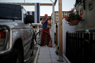 British resident Gerald holds his dog as he stands at the porch of his mobile home at Saydo Park in the outskirts of Mollina