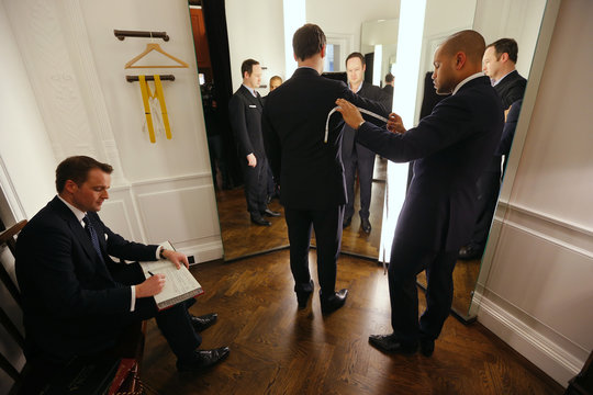 Cutter Ollie Trenchard measures up client James Massey as sales consultant James Field makes notes in a fitting room at bespoke Savile Row tailors Anderson & Sheppard in central London