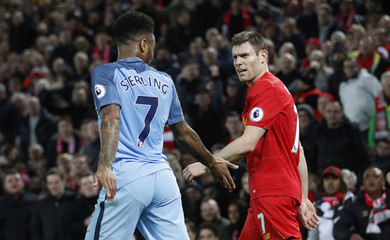 Manchester City's Raheem Sterling clashes with Liverpool's James Milner
