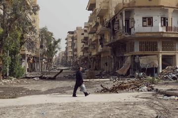 Man walks past damaged houses on a street filled with debris in Deir al-Zor