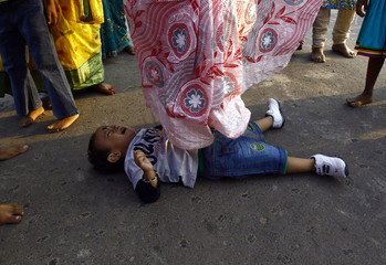 A Hindu woman steps over a child in a ritual seeking blessings for the child from the Sun god Surya during the Chatt Puja festival in Kolkata