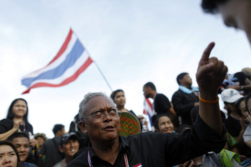 Protest leader and former deputy prime minister Suthep Thaugsuban talks to his staff outside a government complex where anti-government protesters gather