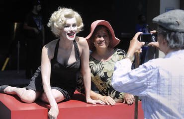 A tourist poses for a picture with a likeness of Marilyn Monroe in Hollywood