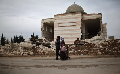 A family walks past a damaged mosque and tank at Azaz city, north Aleppo