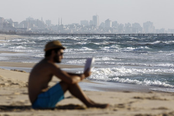 An Israeli man reads a book on Zikim beach at the Mediterranean sea as the northern Gaza Strip is seen in the background