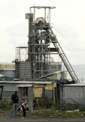 A Khuseleka mine shaft is seen in the background as a couple stands in front of shacks in Sondela township in Rustenburg