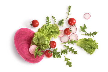 Vegetables in a pink plate on a white background