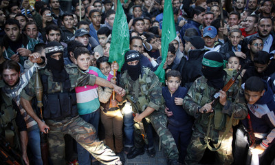 Palestinian members of the al-Qassam brigades hold back the crowd as Hamas chief Meshaal visits the destroyed house of Dalu family in Gaza