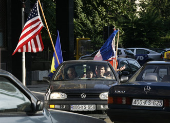 Passengers wave the U.S., Kosovo and British flags as they celebrate in capital Pristina after the World Court said Kosovo's declaration of independence was legal