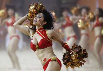 A cheerleader performs a routine during the men's beach volleyball final at the 16th Asian Games in Guangzhou