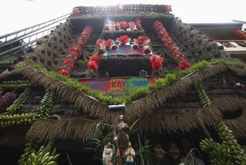 Visitors pose for a picture at a house, which is decorated with assorted fruits and rice grains, during the Pahiyas Festival in Lucban town