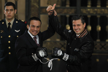 Mexican President Nieto and Mexican boxer Marquez raise their hands while wearing boxing gloves which were used in Marquez's victory over Filipino boxer Pacquiao, during a recognition ceremony at National Palace in Mexico City