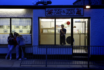 Youths sit outside a fish and chip shop in the town of Lerwick on the Shetland Islands