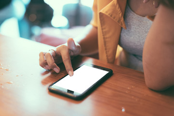 Close up asian girl wearing yellow suit, rings and smart watch using blank screen smart phone in coffee shop in selective focus.