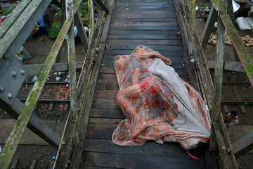Men sleep covered with a mosquito net on a bridge above a train station outside Yangon