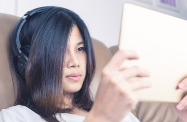 Asian girl with headphone is watching content on tablet