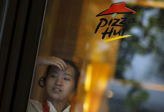 A Pizza Hut employee waits for customers at the entrance of a store in downtown Shanghai