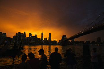 People line a dock in Brooklyn to watch the sun set behind the Manhattan skyline after a summer storm in New York