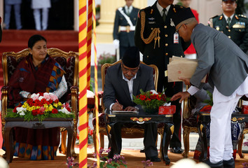 "Newly elected Nepalese Prime Minister Pushpa Kamal Dahal sign oath papers after administrating the oath of office in presence of President Bidhya Devi Bhandari at presidential building ""Shital Niwas"" in Kathmandu"