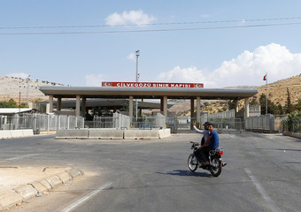 A Syrian man rides a motorcycle at the Turkish Cilvegozu border gate, located opposite the Syrian commercial crossing point Bab al-Hawa, in Reyhanli