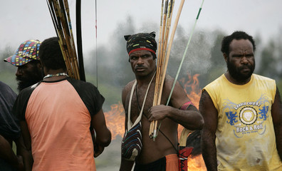 Tribesmen carry bows and arrows as they block a road in Timika