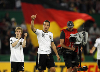 Germany's Marin and Podolski celebrate victory against Azerbaidjan during their Euro 2012 qualifying soccer match in Cologne