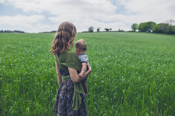Young mother in field with baby