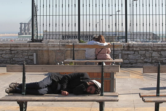 A couple sits on a bench while a man sleeps nearby in front of Algiers port, Algeria