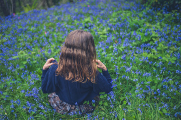 Young woman in meadow of bluebells