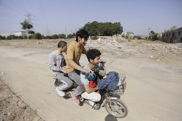 Migrant workers ride an electric bike past the ruins of houses in Beijing