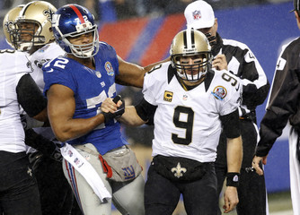 New Orleans Saints quarterback Drew Brees is helped off the turf by New York Giants' defender Osi Umenyiora after Umenyiora sacked Brees during the fourth quarter of their NFL football game in East Rutherford