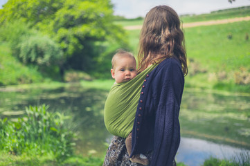 Young woman with baby by pond