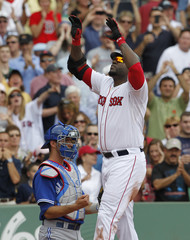 Boston Red Sox's Ortiz celebrates his solo home run at home plate in front of Toronto Blue Jays catcher Arencibia in Boston