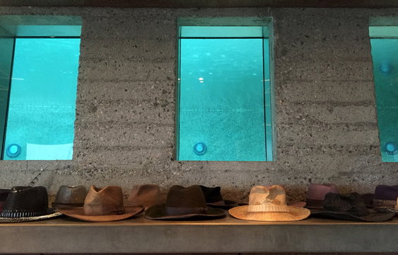 Hats a lined up beneath windows that show the swimming pool at the James Goldstein residence, which was designed by modernist architect John Lautner, during a media event in Los Angeles, California