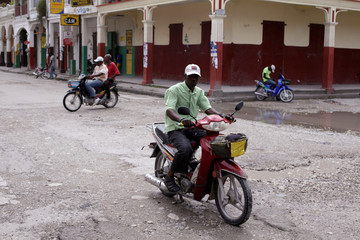 Residents drive motorbikes along a street ahead of Hurricane Matthew in Les Cayes, Haiti