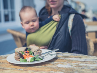 Mother with baby eating sandwich