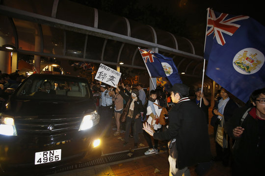 Former Hong Kong Governor Patten sits inside his car as he is greeted by supporters holding colonial Hong Kong flags while leaving the Hong Kong Maritime Museum