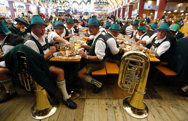 People in traditional Bavarian clothes take a break after the Oktoberfest parade in Munich
