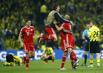 Bayern Munich's players celebrate as dejected Borussia Dortmund players slump onto the grass after their Champions League Final soccer match at Wembley Stadium in London