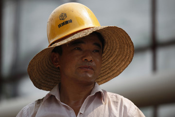 A migrant labourer wears a safety helmet over a straw hat at a construction site in Pinghu