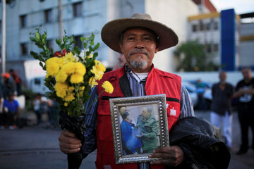 A man holds a picture of Farabundo Marti National Liberation Front Handal and Castro in San Salvador