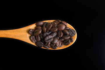 Roasted coffee beans on wood spoon
