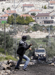 A protester uses a sling to hurl a stone towards Israeli troops during clashes in Kofr Qadoum