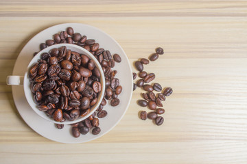 Roasted coffee beans in white cup on wood table